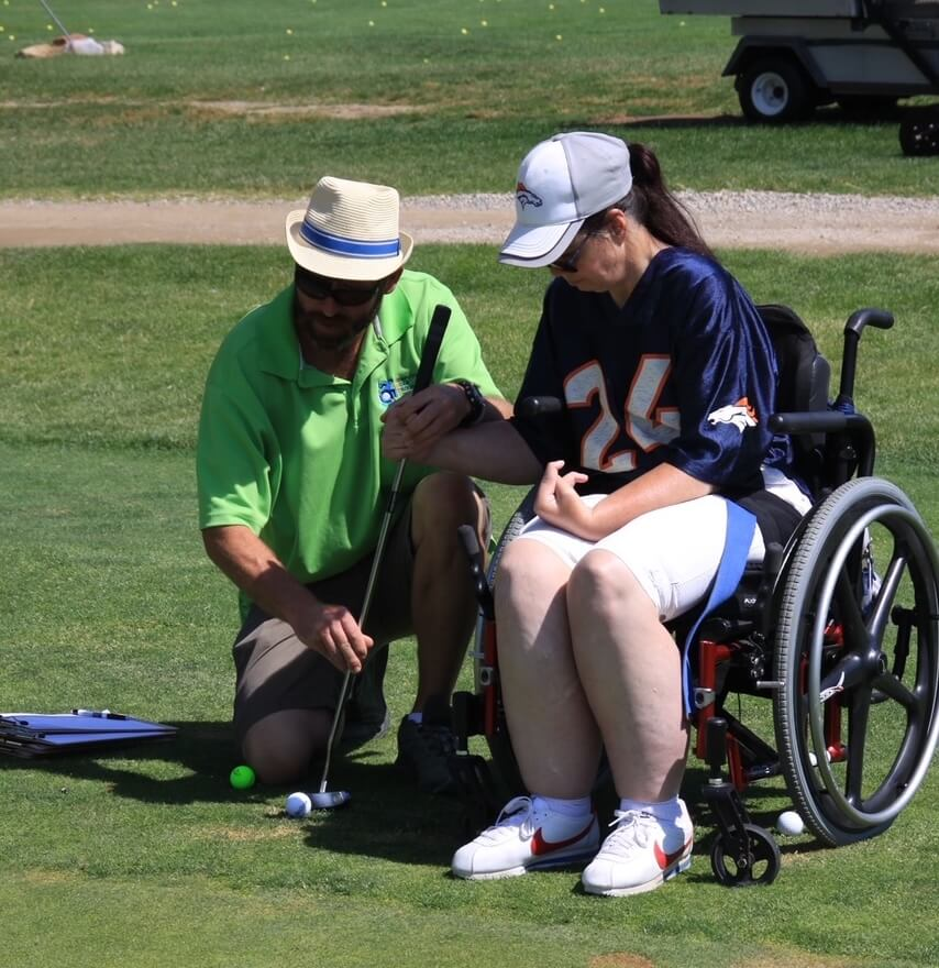 Andy golfing with woman in wheelchair